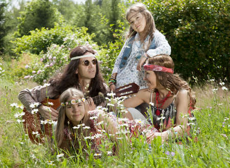 60s hippie: Hippie family sitting in the field and playing guitar