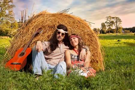 midst: Hippie couple on the haystack in the midst of rural meadow
