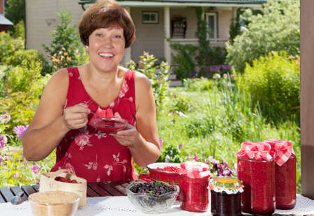mature woman: Happy woman tastes just her cooked raspberry jam