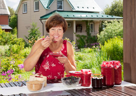 tastes: Middle aged woman tastes just her cooked raspberry jam