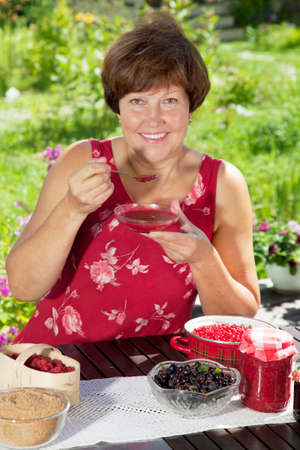 tastes: Middle aged Caucasian woman tastes just her cooked raspberry jam Stock Photo