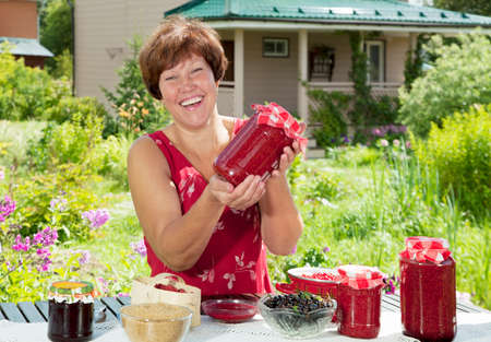 prepare: Happy woman show to camera just her cooked raspberry jam-jar