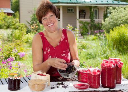 mermelada: Mujer que hace la mermelada casera de bayas y sonriendo a la cámara