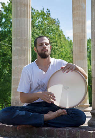 pandero: Joven tocando la pandereta en un parque de la ciudad en un día soleado de verano