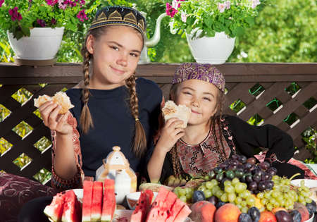 skullcap: Two little girls dressed in Central Asian clothes have breakfast at chaikhana Stock Photo