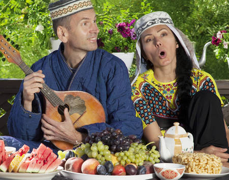 mandolin: Couple dressed in Uzbekistan clothes playing mandolin and singing during breakfast Stock Photo