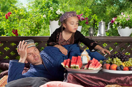 summerhouse: Father with his daughter have breakfast at Uzbekistan chaikhana summer-house