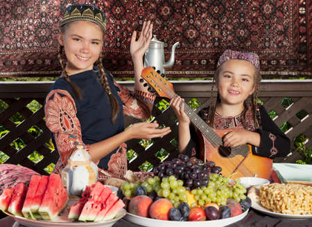 mandolin: Two little girls dressed in Central Asian clothes playing mandolin and dancing during breakfast at chaikhana (Uzbekistan summerhouse)