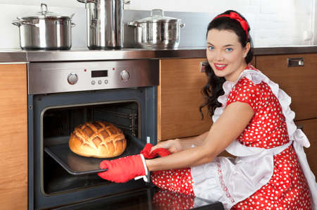 baking bread: Young pretty housewife baking bread in kitchen oven Stock Photo
