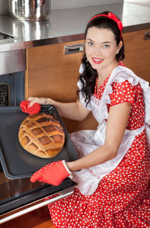 baking bread: Happy young housewife holding baking tray with bread Stock Photo