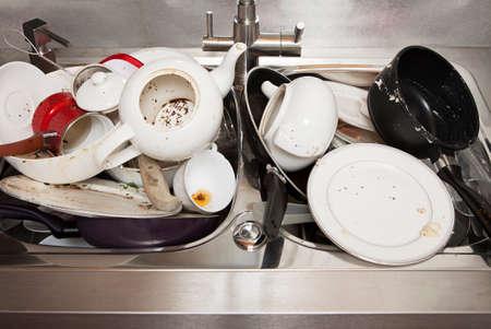 lavar trastes: Pila de platos sucios en el fregadero de la cocina