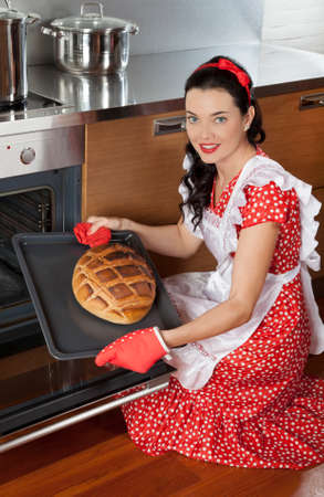 young beautiful woman: Beautiful brunette housewife holding baking tray with bread
