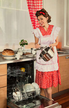 loads: Housewife loads the dishes in the dishwasher. 1950s style post processing emulation. Stock Photo