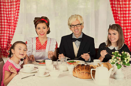 emulation: Happy family have breakfast. Intentional 1950s style post processing emulation. Stock Photo