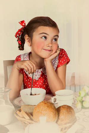 emulation: Little girl has breakfast at home. Intentional 1950s style post processing emulation.
