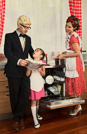 emulation: The head of the family reading newspaper in a kitchen. Intentional 1950s style post processing emulation. Stock Photo