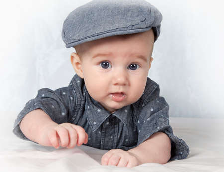 lying on his tummy: Portrait of adorable child in cap lying on his tummy Stock Photo