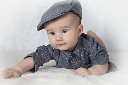 lying on his tummy: Bright portrait of adorable child in cap lying on his tummy Stock Photo