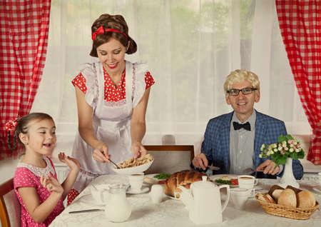 comiendo pan: La vendimia labró la familia tiene el desayuno en casa. Monocromo, texturas grunge, intencional estilo de la década de 1900