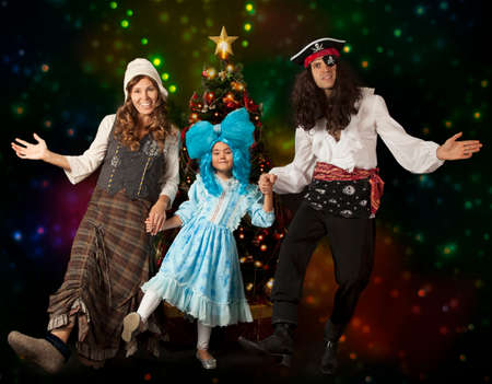 christmas funny: Funny family in carnival costumes dancing in front of Christmas tree Stock Photo