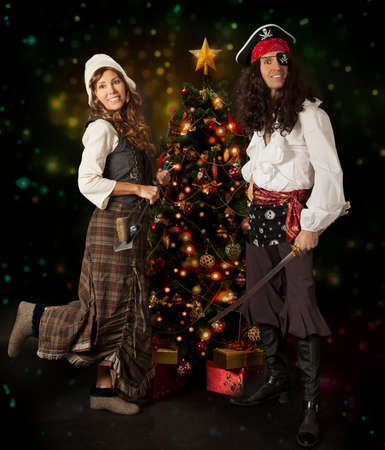 female pirate: Picture of a carnival couple posing over Christmas tree on a colorful background with glowing lights