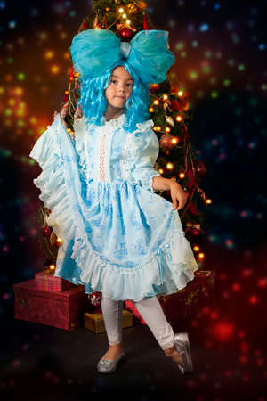 christmas costume: Little girl in carnival costume of fairy with blue hair in front of Christmas tree