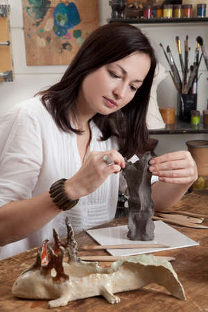 Artisan woman modeling a clay sculpture in a studio