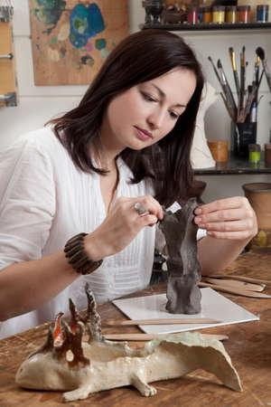 artist: Artisan woman modeling a clay sculpture in a studio
