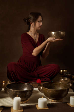 bronze bowl: Young woman with Tibetan singing bowl in front of brown background