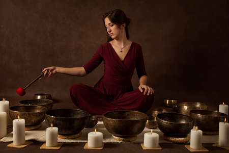 Young woman relaxing with Tibetan singing bowls in front of brown background