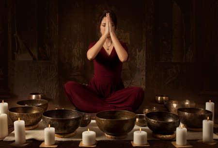 Jonge vrouw mediteert alvorens te spelen op Tibetaanse klankschalen