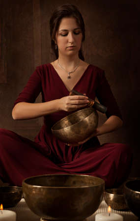 bronze bowl: Woman playing a Tibetan bowl, traditionally used to aid meditation in Buddhist cultures Stock Photo