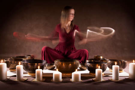 bronze bowl: Long time exposure photo of a woman playing a Tibetan bowls, focus on a singing bowls