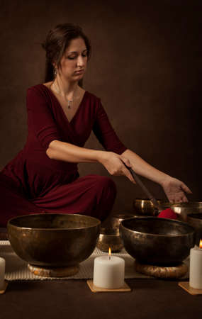 singing bowl: Woman with Tibetan singing bowl in front of brown background Stock Photo