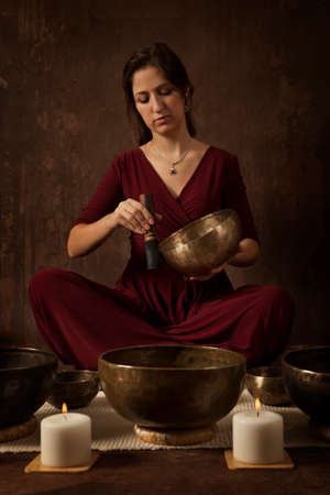 bronze bowl: Woman playing a singing bowls also known as Tibetan Singing Bowls, rin gongs, Himalayan bowls or suzu gongs