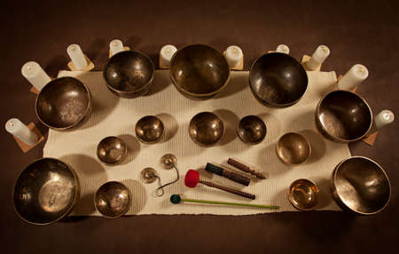 Set of Tibetan singing bowls and bells with burning candles