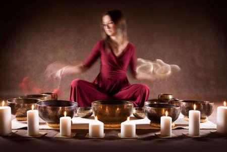 Blur motion foto van een vrouw die een Tibetaanse kommen speelt, focus op een zang kommen