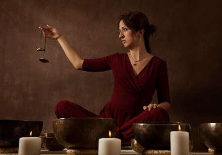 singing bells: Woman playing Tibetan bells (tingsha) for begin meditation session