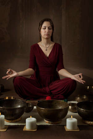 singing bowls: Woman  practice meditation with Tibetan singing bowls in front of brown background Stock Photo
