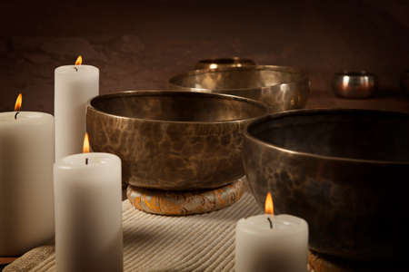 Tibetan singing bowls with burning candles close-up