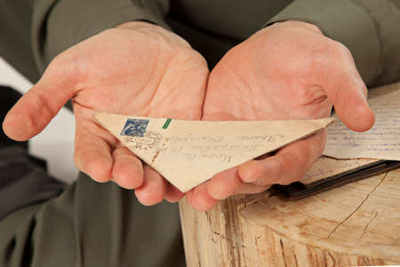 may 9: Soldier hands holding a letter from the Second World War close-up