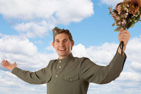 may 9: Soviet soldier in uniform of World War II holding a bunch of flowers on the blue sky background