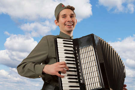 Soviet soldier in uniform of World War II playing the accordion on the blue sky background Stock Photo