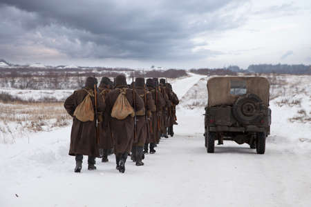 A company of Soviet soldiers dressed in the uniform of World War II are in a winter field