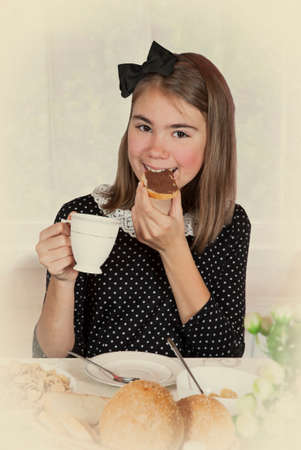 spread: Beautiful teenage girl eating chocolate spread at breakfast time. Monochrome, grunge textures, intentional styled to the 1950 Stock Photo