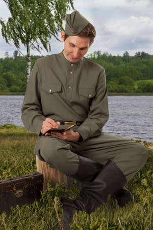 letter writing: Soviet soldiers in uniform of World War II sitting on a stump while writing a letter to home Stock Photo
