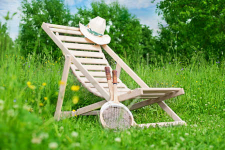 grass plot: Chaise-longue with a hat and badminton rackets in the middle of the meadow