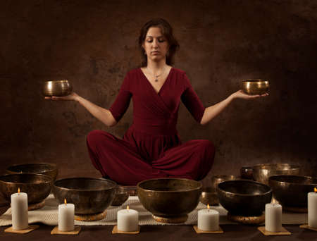 bronze bowl: Young woman with Tibetan singing bowls in her hands in front of brown background Stock Photo