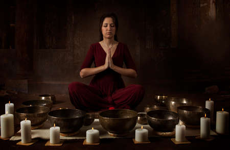bronze bowl: Young woman meditates before playing on Tibetan singing bowls indoors