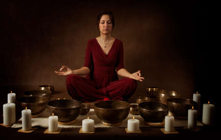 singing bowls: Young woman  practice meditation with Tibetan singing bowls in front of brown background Stock Photo